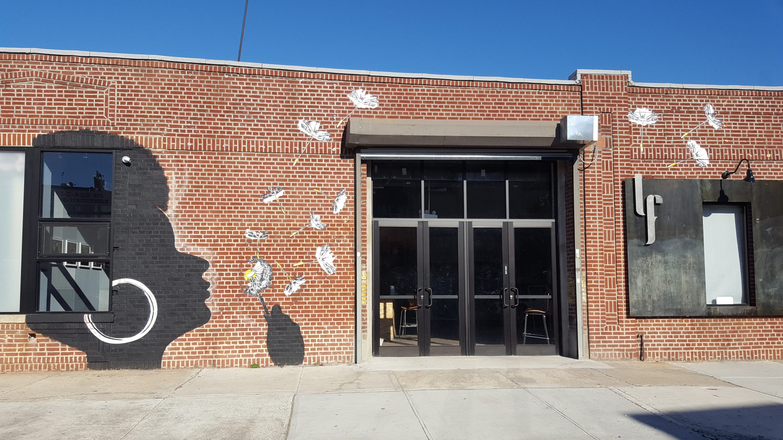 exterior photo of littlefield with mural of woman with afro and big hoop earrings blowing a dandelion